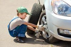 男孩更换轮子 免版税图库摄影
