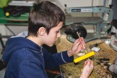 男孩绘画木项目黄色 免版税库存图片