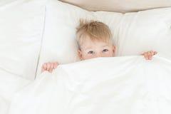 男孩从毯子下面 免版税库存图片