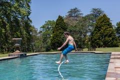 男孩水池跳跃 免版税库存图片