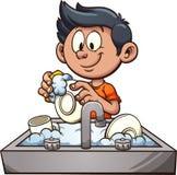 男孩洗涤的盘 免版税图库摄影