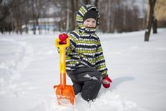 男孩以清除雪的大铁锹 免版税库存图片