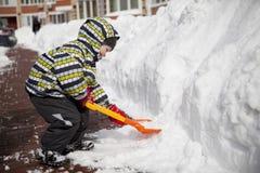 男孩以清除雪的大铁锹 免版税库存照片