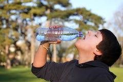 男孩渴热切地饮用水 图库摄影