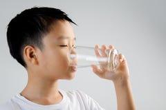 男孩从玻璃的饮料水 免版税库存照片