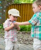 男孩给他的兄弟一个复活节彩蛋 免版税图库摄影