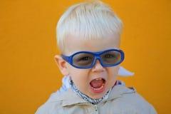 男孩戴眼镜,并且他呼喊 免版税库存图片
