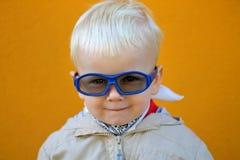 男孩戴眼镜,并且他微笑 免版税库存图片