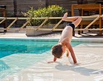 男孩翻筋斗在水中 免版税库存图片