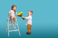 男孩给花束在蓝色背景隔绝的女孩 免版税库存图片