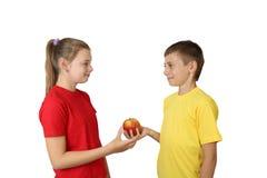 男孩给苹果女孩 库存图片