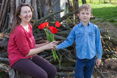 男孩给郁金香他的祖母 免版税库存照片
