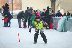 男孩滑雪在市中心 免版税库存图片