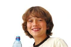 男孩drinkng微笑的少年水 库存照片