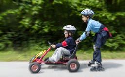 男孩gokart和直排轮式溜冰鞋 免版税库存照片
