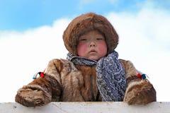 男孩Nenets全国礼服的驯鹿牧民在天空backgrou 库存照片