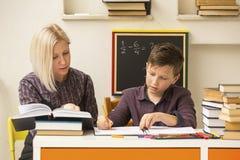 男小学生做与家庭教师的允诺的家庭作业 帮助 免版税图库摄影