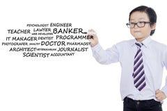 男小学生写他的未来工作 免版税库存照片