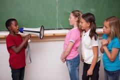 男小学生叫喊通过扩音机对他的同学 免版税库存照片