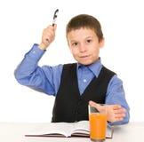 男小学生喝汁液在有日志和笔的一张书桌 免版税库存图片