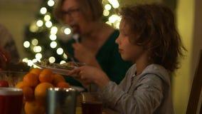 男小学生在与他的祖父母的圣诞节桌上一棵新年树的背景的 男孩提供他的板材 影视素材