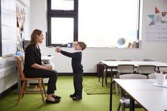 男小学生在提出礼物的小学对他的女老师在教室,全长,侧视图 免版税库存图片