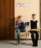 男小学生在校长的旁边坐 免版税库存图片