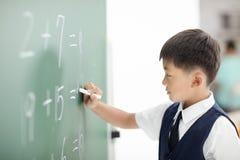 男小学生在黑板的文字答复 免版税库存图片
