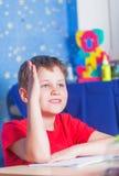 男小学生培养他的手 免版税库存照片