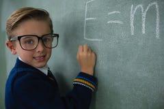 男小学生文字在黑板的算术惯例 免版税库存照片