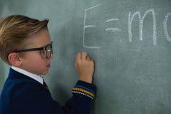 男小学生文字在黑板的算术惯例 免版税图库摄影