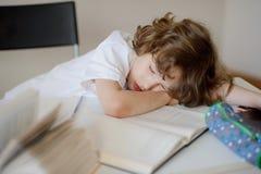 男小学生有睡着的开会在学校书桌 免版税库存照片