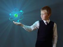 男小学生藏品发光的原子 免版税库存照片