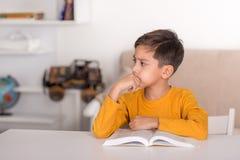 男小学生读课本并且认为 免版税库存图片