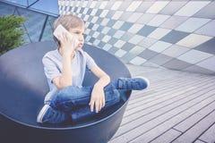 男小学生谈话在电话在城市 图库摄影