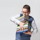 男小学生负担重的堆书 免版税图库摄影