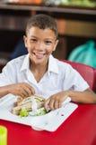 男小学生画象吃午餐在断裂时间 免版税图库摄影