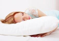男式晚礼服的妇女睡觉在白色枕头的 库存照片