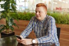 年轻男性一张斜向一边的画象安排红色头发和时髦发型穿戴在控制中拿着智能手机的衬衣,当坐在t时 免版税库存照片