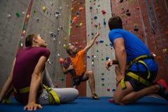 男性上升在健身房的墙壁的教练员引导的运动员 免版税库存照片