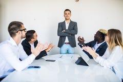 男性上司发言在会议室表附近 小组工作 免版税库存图片