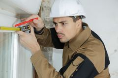 男性与卷尺的建筑工人建造者测量的门框 库存图片