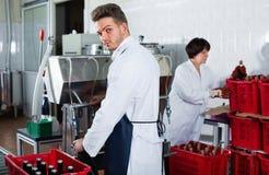 男性与机器的工作者装瓶的酒在汽酒工厂 库存图片