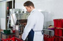 男性与机器的工作者装瓶的酒在汽酒工厂 库存照片