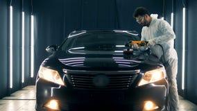 男性专家抛光有一台特别仪器的汽车的敞篷 影视素材