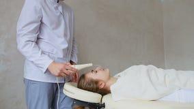 男性专家的化妆师展示按摩设备工作面孔的在耐心` s女孩背景,在长沙发说谎 影视素材