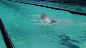 男性严谨地在接踵而来的体育运动游泳竞赛的蝶泳被训练 活动公共 股票录像