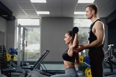 男性个人教练员帮助的妇女与重的哑铃一起使用在健身房 免版税库存照片