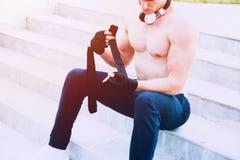 年轻男性为坚硬锻炼做准备和投入他的手套为 免版税图库摄影