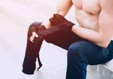 年轻男性为坚硬锻炼做准备和投入他的手套为 库存照片